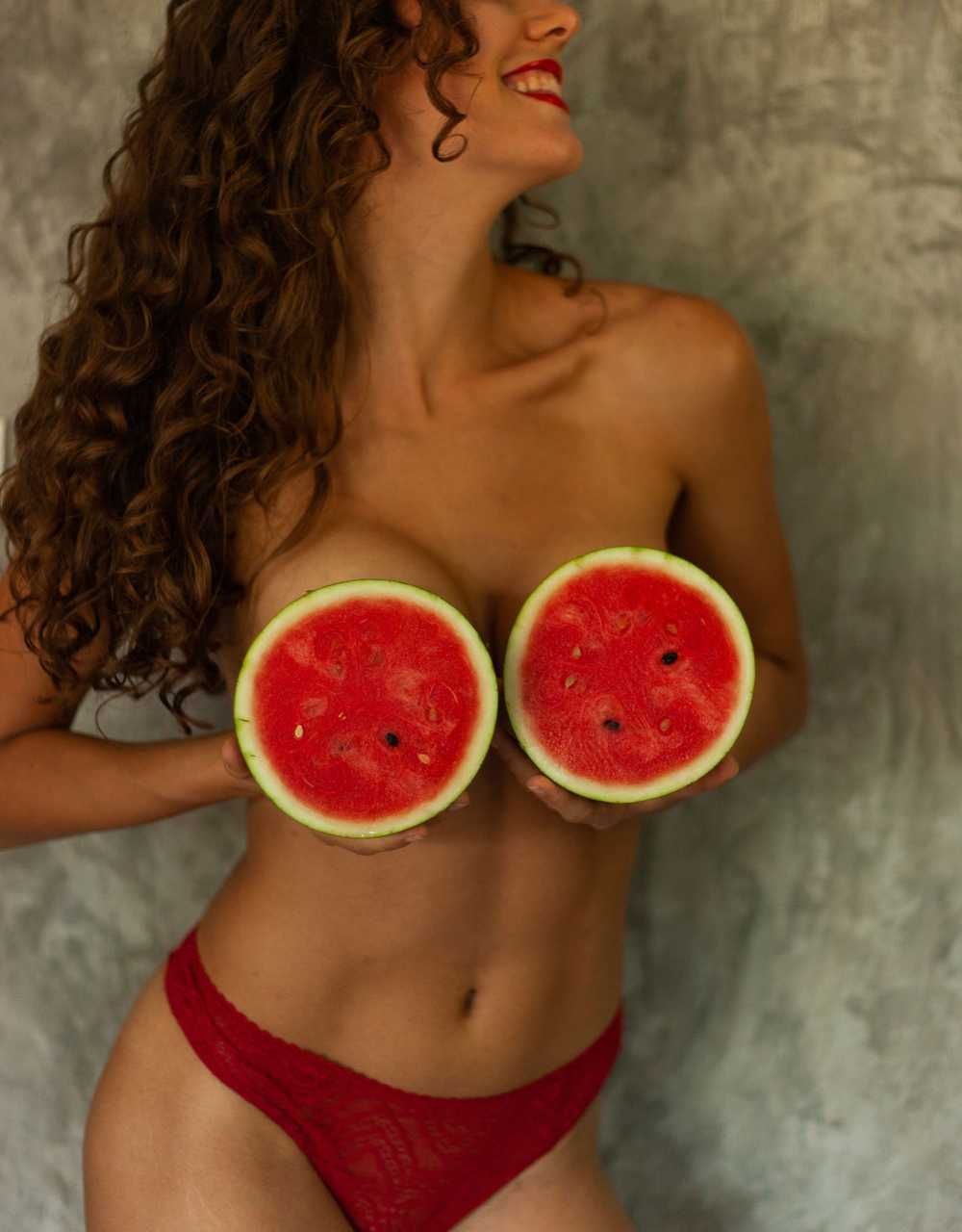 topless woman with sliced orange on her breast