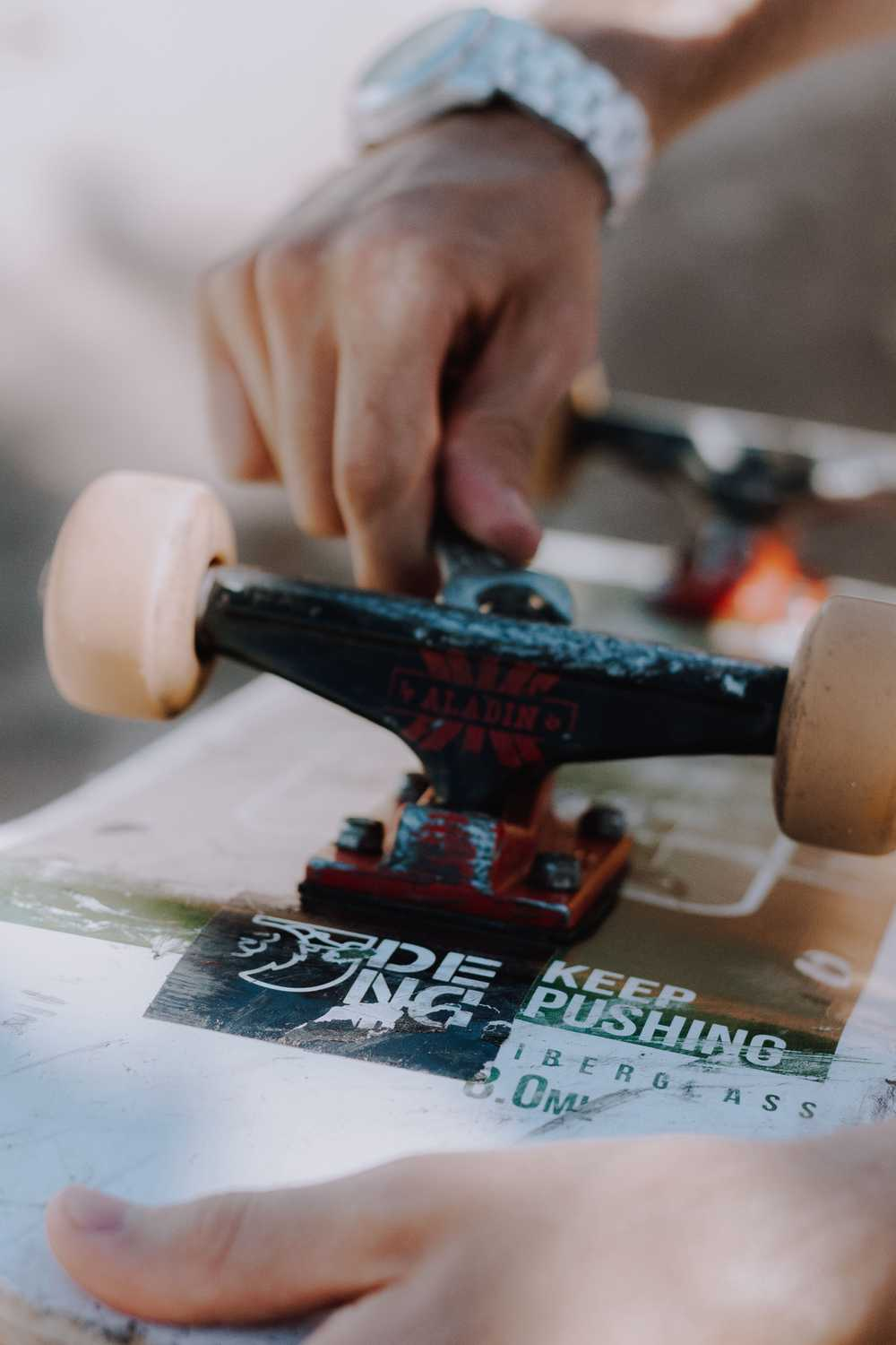 close-up photo of person repairing skateboard