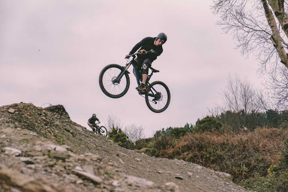 man riding mountain bike by slope during daytime