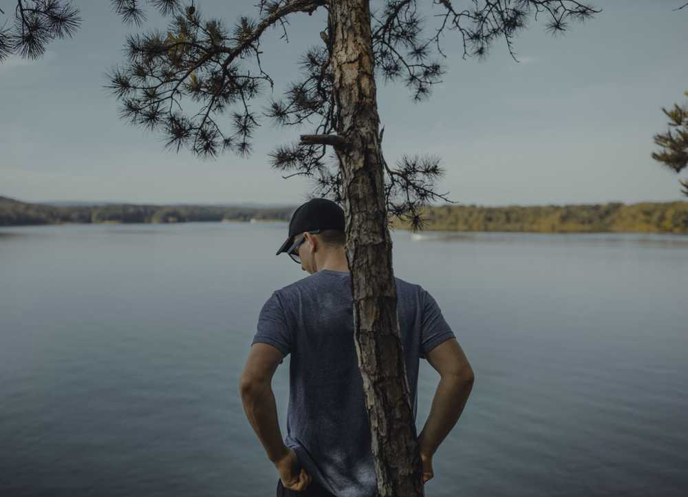 man standing near tree and body of water