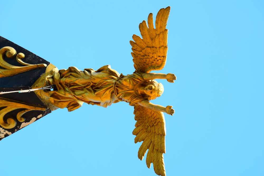 gold angel statue under blue sky during daytime