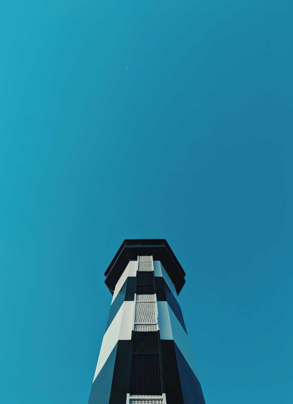 white and blue lighthouse in low-angle photography during daytime