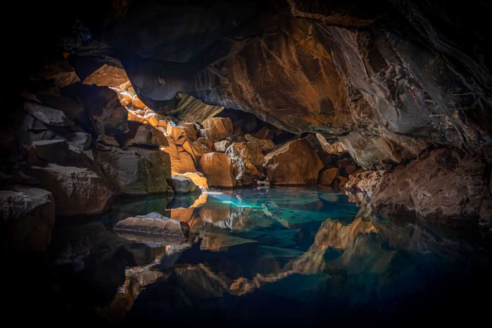 cave surrounded with blue body of water