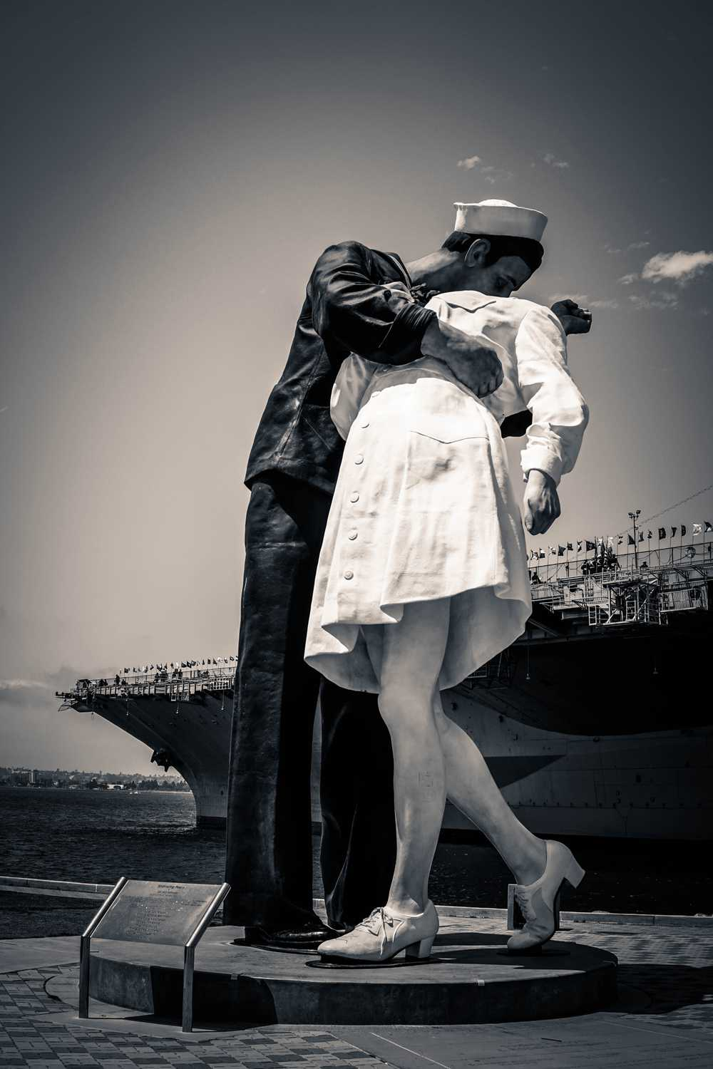 grayscale photo of man kissing woman statue