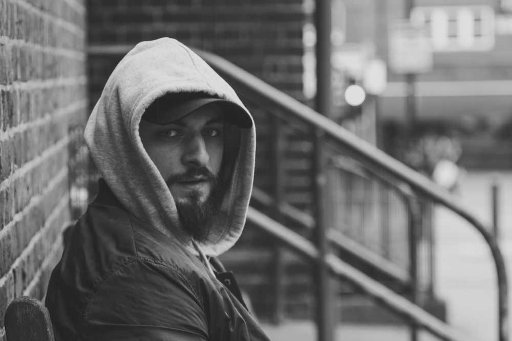 grayscale photography of man wearing hoodie