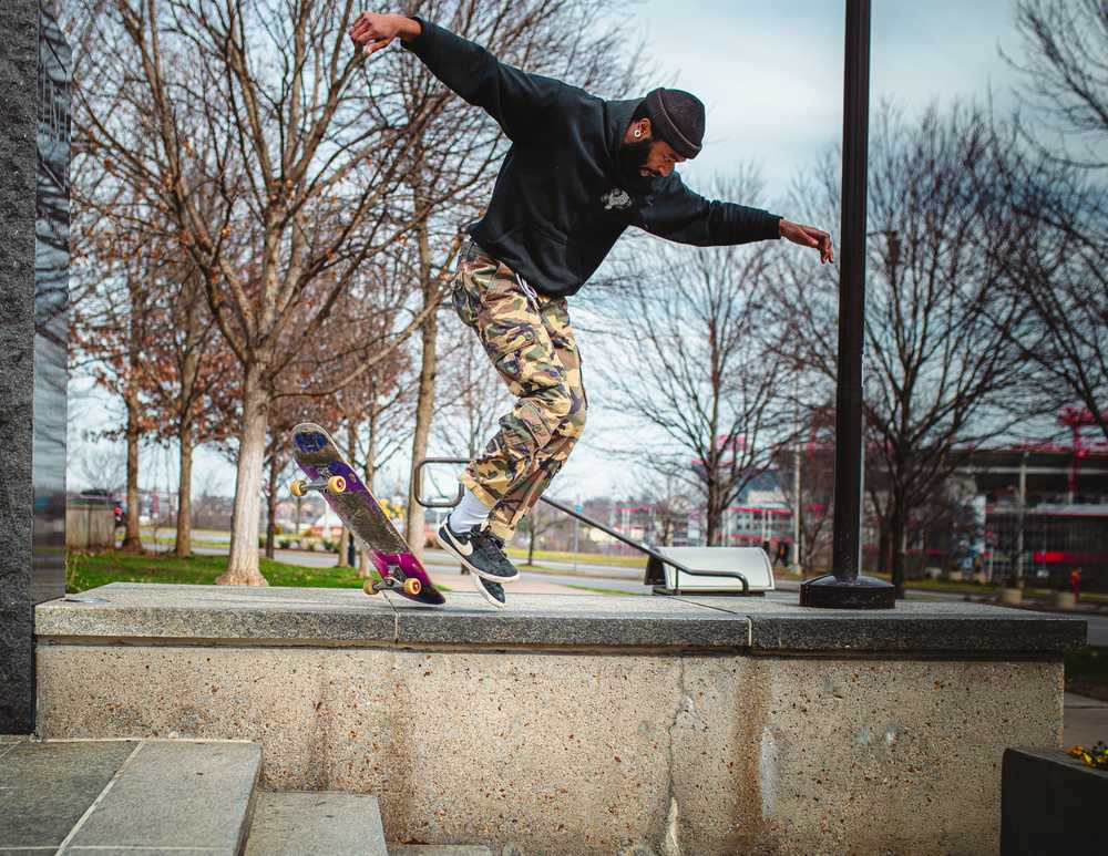man in black jacket and brown pants jumping on skateboard during daytime