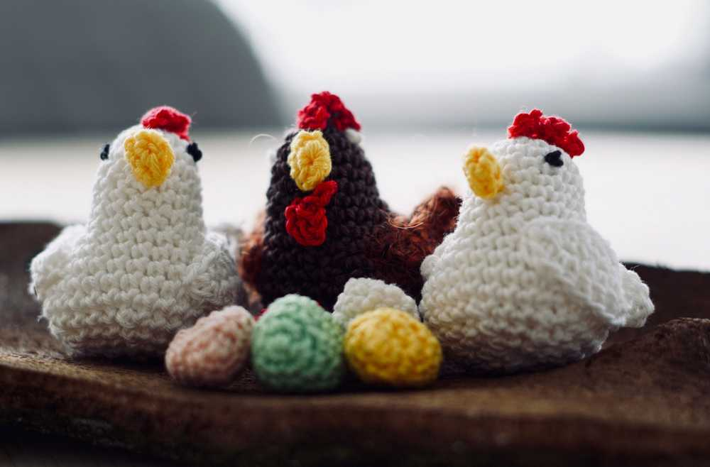three knit chicken figures on brown wood