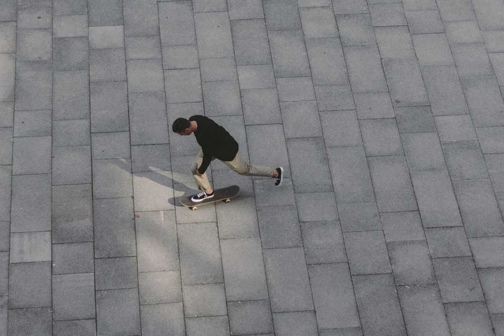 man skateboarding on concrete pavement