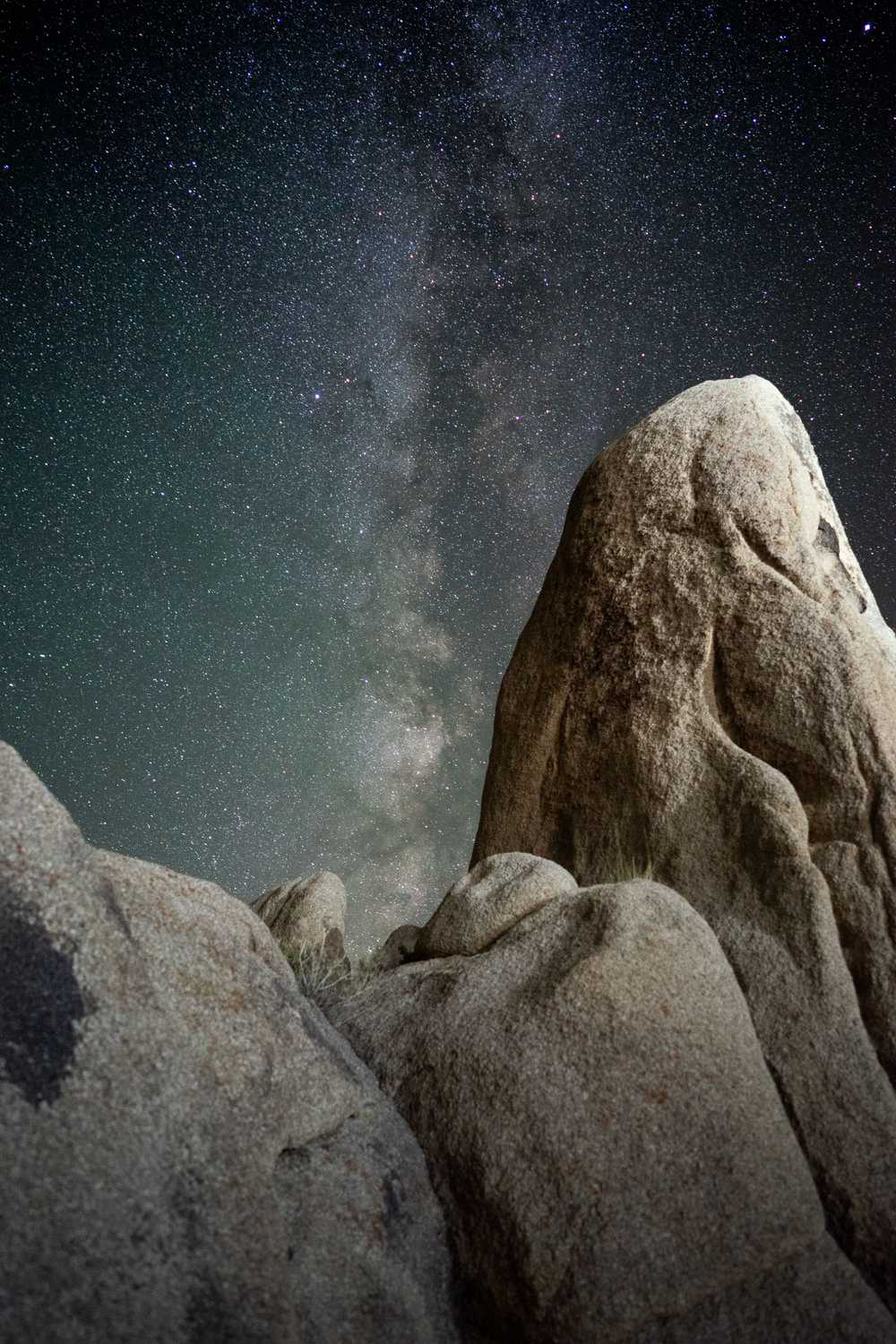 brown rock formations under starry night