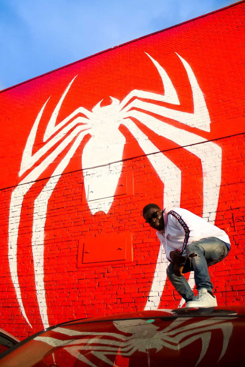 man standing in front of Spider-Man wall