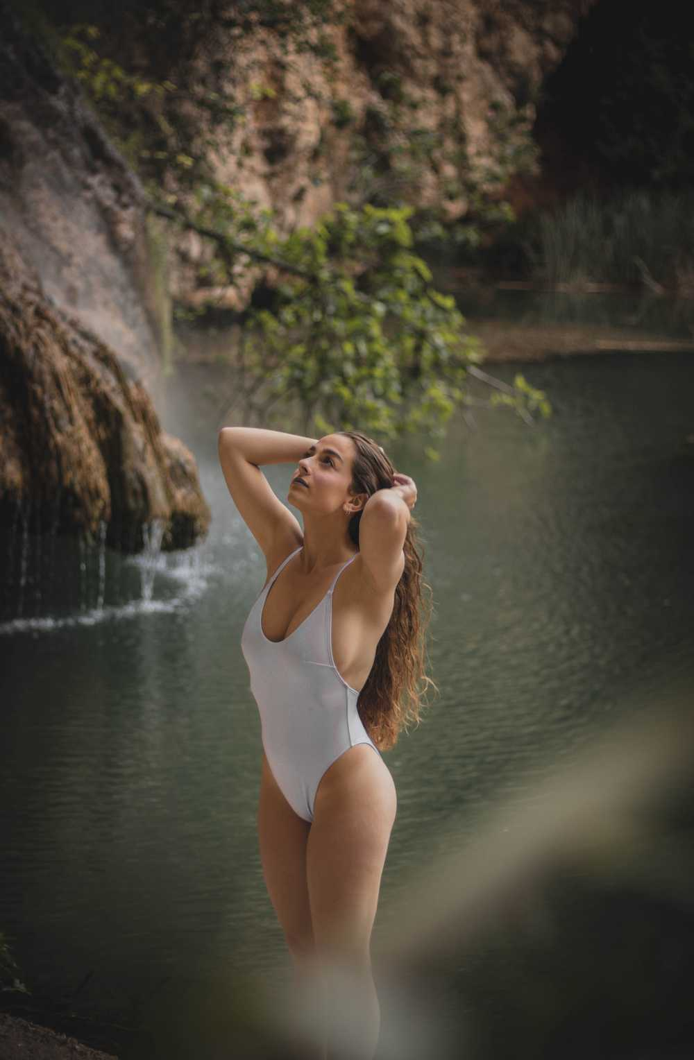 woman wearing white swimsuit standing near body of water