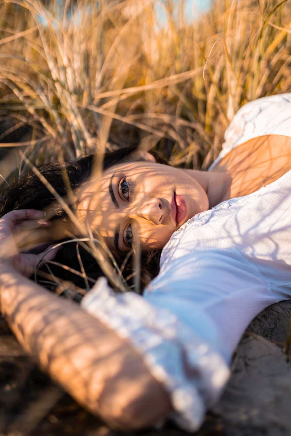 woman in white shirt lying on brown grass