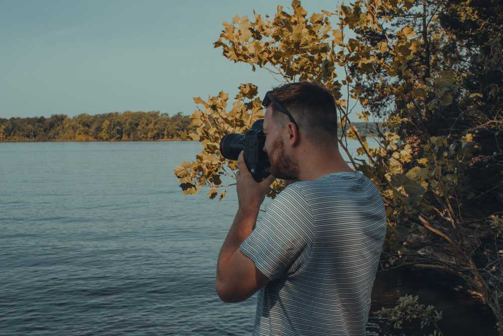 man holding camera near body of water