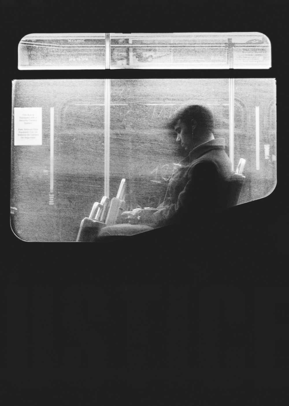 Black and white shot of man sitting on night bus through dirty window in Boston