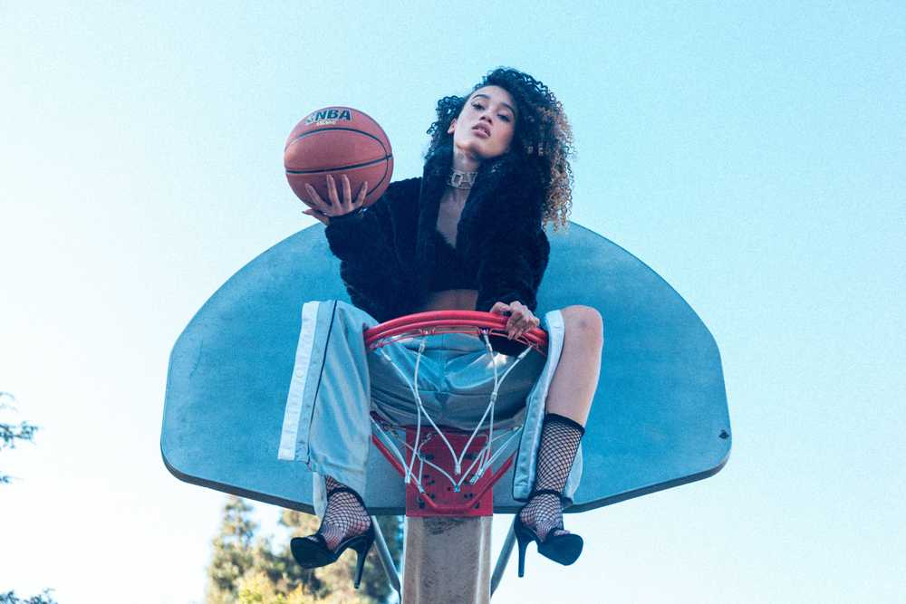 woman sitting on basketball hoop holding basketball at daytime