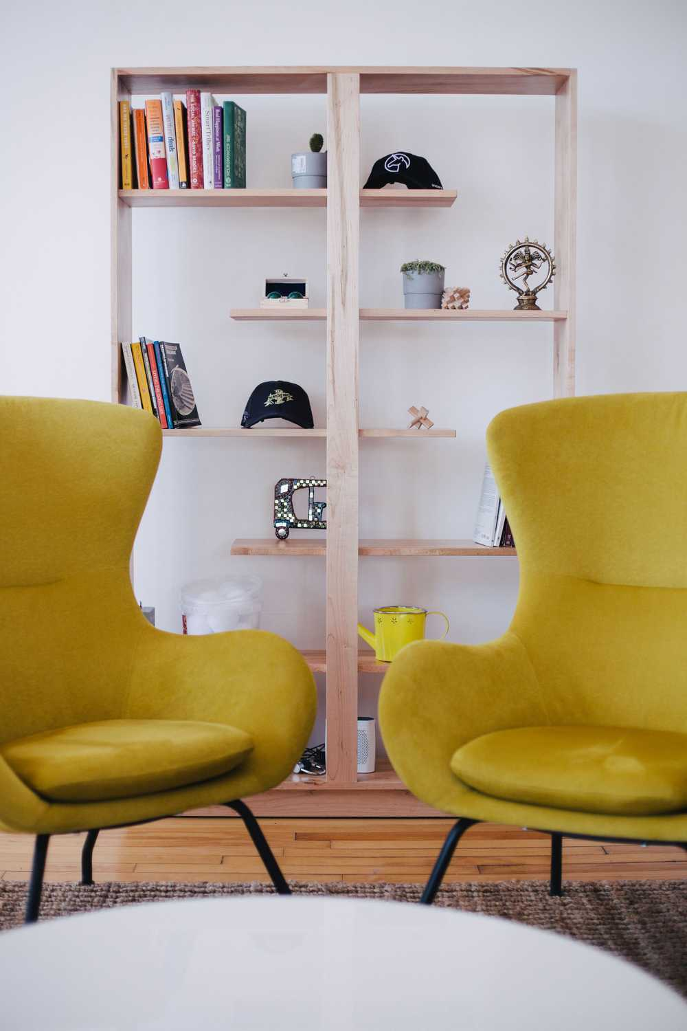 two yellow chairs near brown shelf