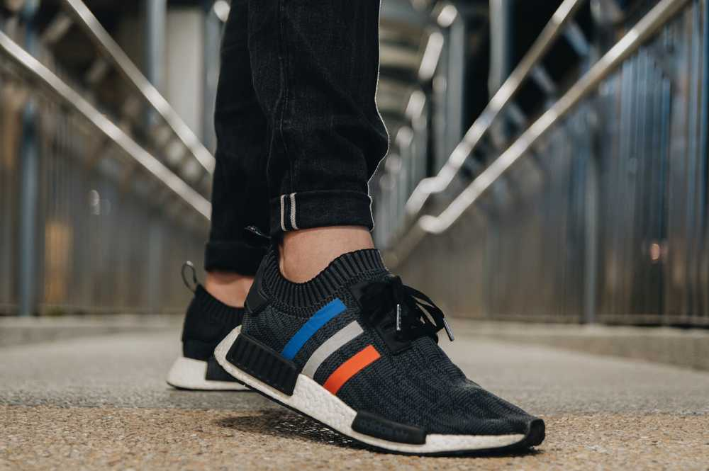 person wearing black Adidas shoes