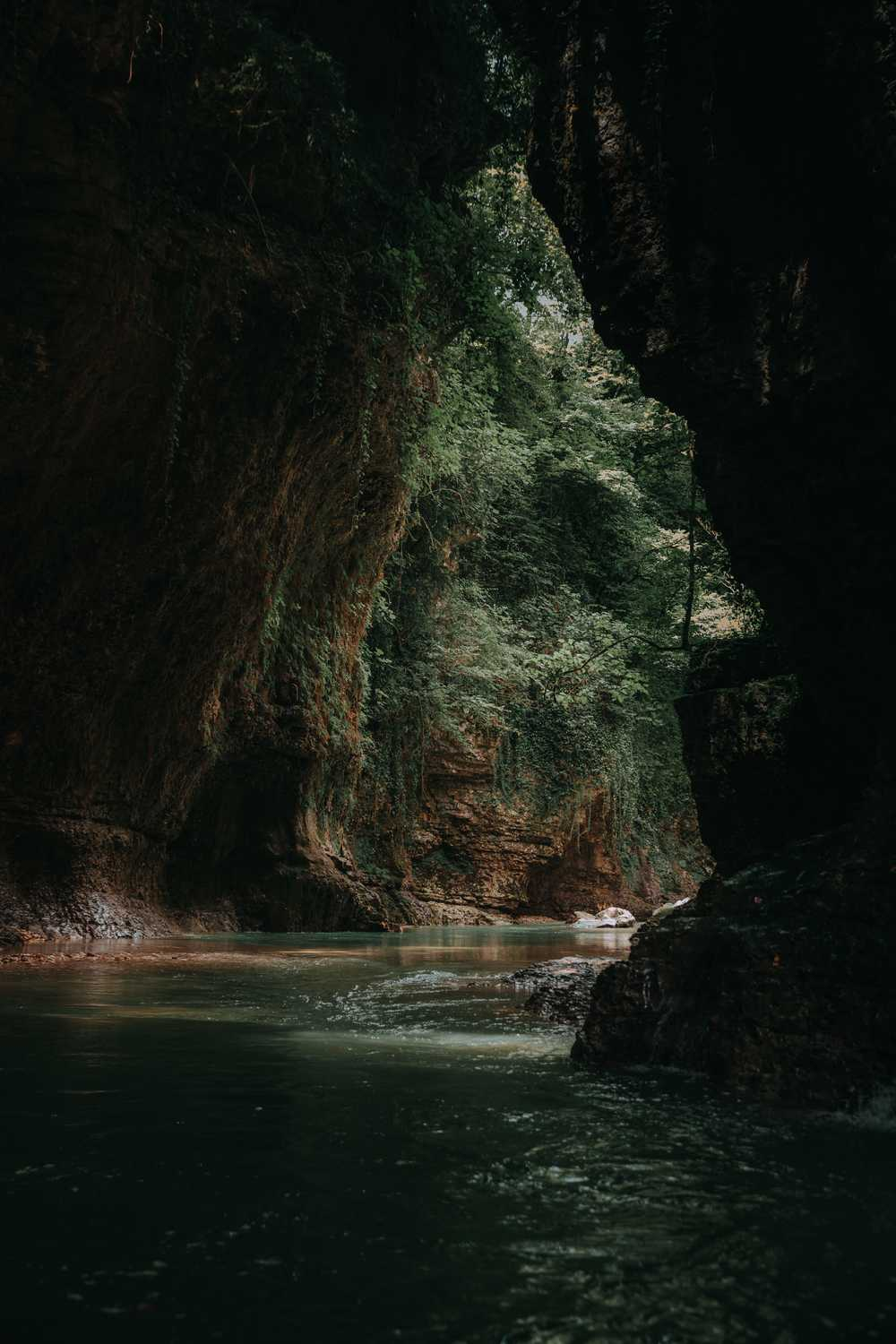 calm body of water inside cave at daytime