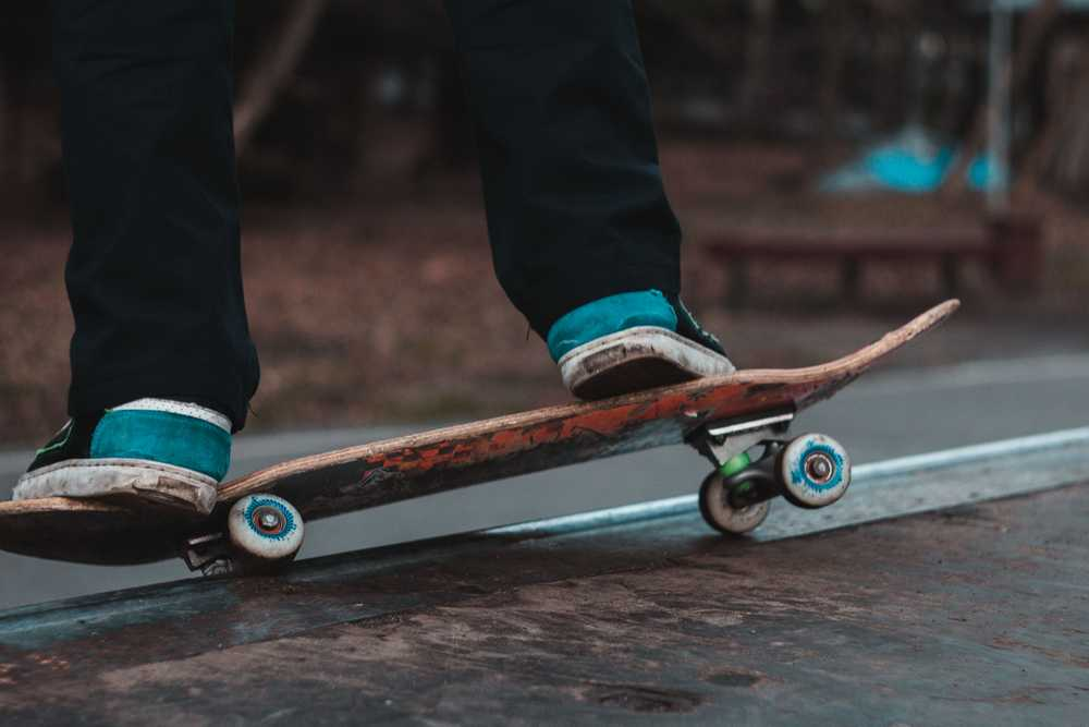 person in black pants riding on brown skateboard