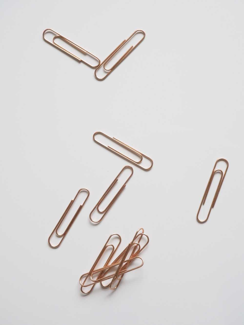 brown paper clips on white surface