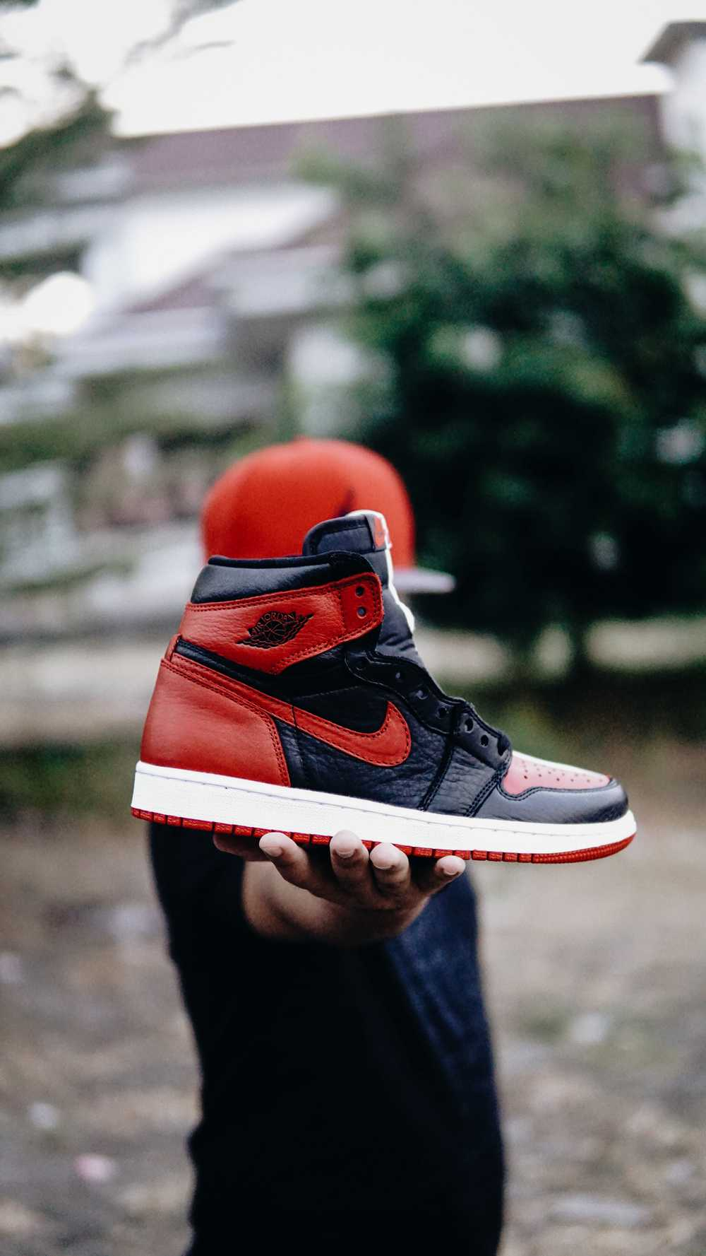 selective focus photo of person holding unpaired black and red Nike Air Jordan 1 shoe