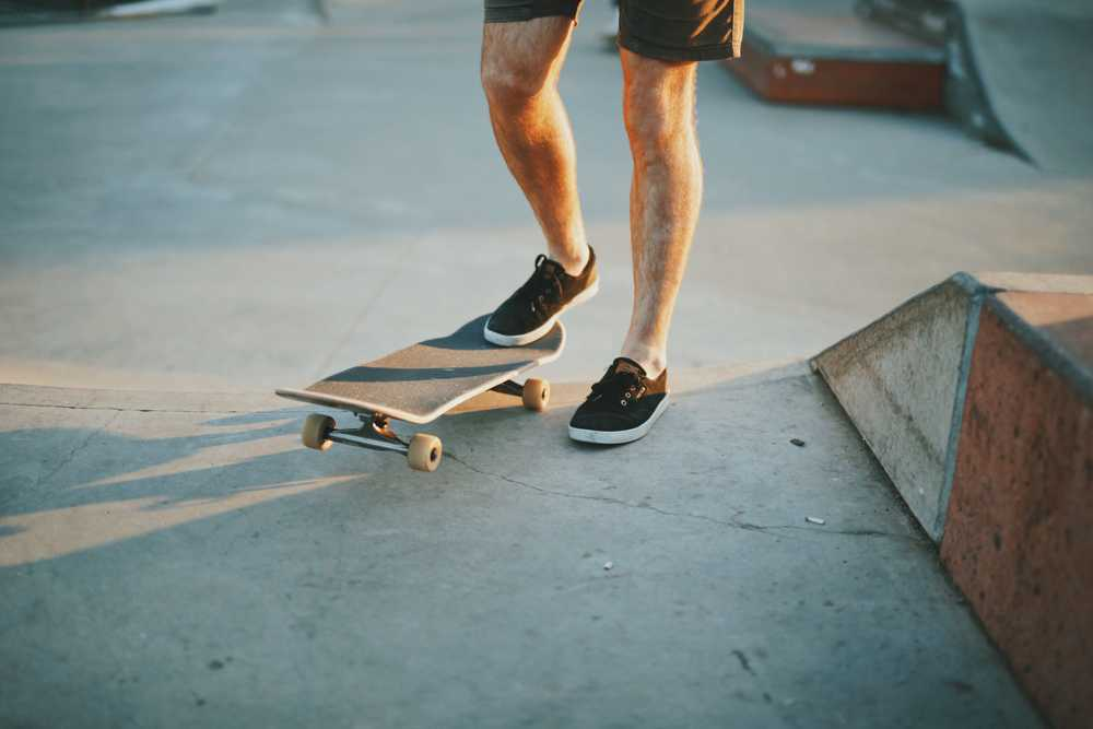 person in black low-top sneakers stepping on black skateboard near brown wooden skateboard ramp during daytime
